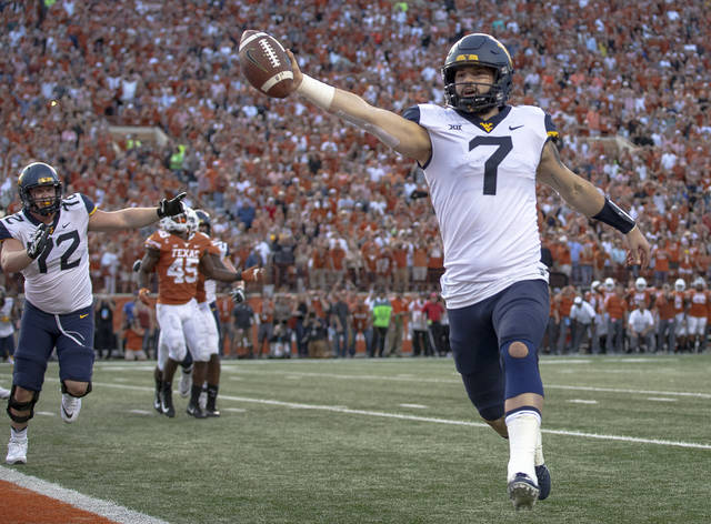 West Virginia quarterback Will Grier (7) scores the game-winning two-point conversion during an NCAA college football game against Texas in Austin, Texas, on Saturday, Nov. 3, 2018. West Virginia defeated Texas 42-41. (Nick Wagner/Austin American-Statesman via AP)