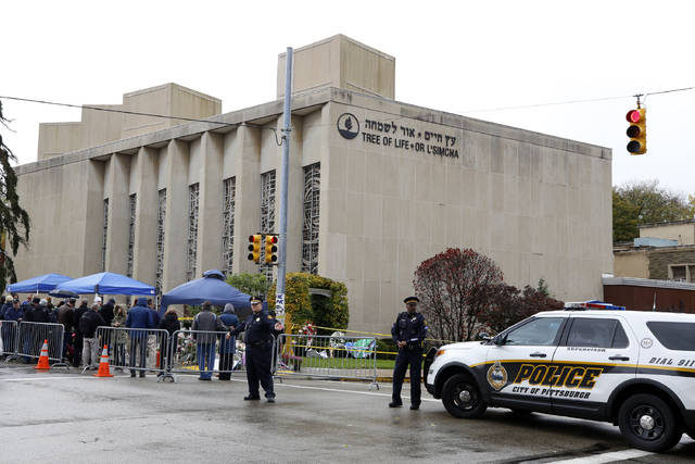 Pittsburgh Police direct traffic as their vehicles close the street adjacent to the Tree of Life Synagogue on Saturday, Nov. 3, 2018, as a curbside Shabbat morning service is held on the street corner in the Squirrel Hill neighborhood of Pittsburgh. The service honored the 11 people killed by a gunman, Oct 27, 2018 while worshipping at the Tree of Life Synagogue. (AP Photo/Gene J. Puskar)