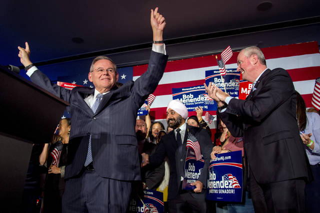 U.S. Sen. Bob Menendez celebrates his re-election in Hoboken, N.J., Tuesday, Nov. 6, 2018, while Gov. Phil Murphy stands at right. (Tom Gralish/The Philadelphia Inquirer via AP)