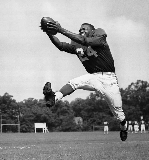 FILE - In this July 30, 1953, file photo, veteran halfback Wally Triplett of Penn State U., originally from La Mott, Pa., poses in action during his second year with Chicago Cardinals and fourth year in the National Football League. Triplett, who left his indelible mark on NFL history by becoming the first African-American player to be drafted and play for an NFL team, passed away Thursday, Nov. 8, 2018, the Detroit Lions announced. He was 92. (AP Photo/File)