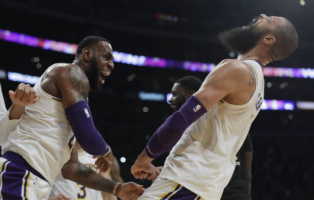 Los Angeles Lakers' Tyson Chandler, right, celebrates with teammate LeBron James after Chandler blocked a shot from Atlanta Hawks' Trae Young as time expired in the NBA basketball game Sunday, Nov. 11, 2018, in Los Angeles. Los Angeles won 107-106. (AP Photo/Marcio Jose Sanchez)