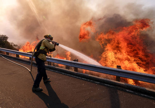 A firefighter battles a fire along the Ronald Reagan Freeway, aka state Highway 118, in Simi Valley, Calif., Monday, Nov. 12, 2018. (AP Photo/Ringo H.W. Chiu)