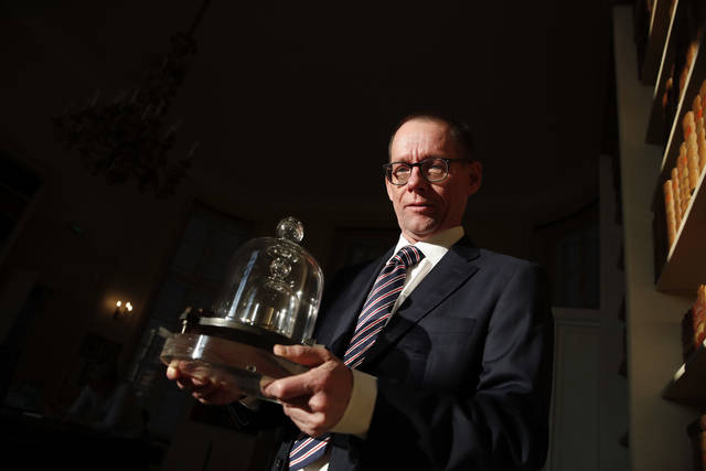 In this photo taken Wednesday, Oct. 17, 2018., the head of BIPM (International Bureau of Weights and Measures) Martin J.T. Milton holds a replica of the International Prototype Kilogram in Sevres, near Paris. The golf ball-sized metal cylinder at the heart of the world's system for measuring mass is heading into retirement. Gathering this week in Versailles, west of Paris, governments on Friday Nov. 16, 2018, are expected to approve a plan to instead use a scientific formula to define the exact weight of a kilo. (AP Photo/Christophe Ena)