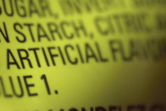 "This Thursday, Nov. 8, 2018 photo shows part of an ingredient label, which lists ""artificial flavoring,"" on a packet of candy in New York. In November 2018, the U.S. Food and Drug Administration has decided to give companies two years to purge their products of the six ingredients, described only as ""artificial flavors"" on packages. The words ""artificial flavor"" or ""natural flavor"" refer to any of thousands of ingredients. (AP Photo/Patrick Sison)"