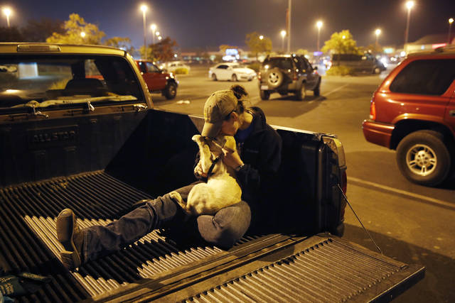 Sarah Gronseth kisses her dog Branch in the bed of a truck in a parking lot, Tuesday, Nov. 13, 2018, in Chico Calif. Gronseth, a teacher, evacuated some of her high school students in her truck as the fire bore down on the high school in Paradise, Calif. She lost her home in the fire. (AP Photo/John Locher)