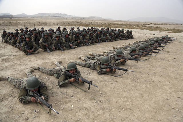 In this Oct. 31, 2018 photo, a group of Afghan National Army soldiers watch others participate in a live fire exercise at the Afghan Military Academy, in Kabul, Afghanistan. When U.S. forces and their Afghan allies rode into Kabul in November 2001 they were greeted as liberators. But after 17 years of war, the Taliban have retaken half the country, security is worse than it's ever been, and many Afghans place the blame squarely on the Americans. (AP Photo/Rahmat Gul)