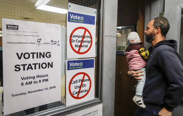 A Calgarian arrives to vote in a plebiscite, Tuesday, Nov. 13, 2018, in Calgary, Alberta, on whether the city should proceed with a bid for the 2026 Winter Olympics. (Jeff McIntosh/The Canadian Press via AP)