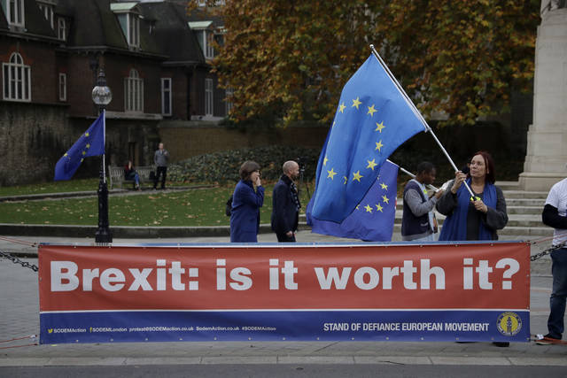 An anti-Brexit supporter holds a European flag by a banner across the street from the Houses of Parliament in London, Thursday Nov. 15, 2018. Leading Brexiteer Jacob Rees-Mogg has submitted a letter of no confidence in Theresa May, as the Prime Minister reels from the loss of four ministers - including two from her Cabinet - in protest at her Brexit plans. (AP Photo/Matt Dunham)