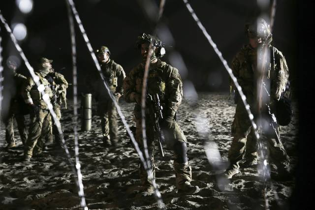 U.S. Border Patrol agents stand on the U.S. side of the border, seen through the concertina wire where the border meets the Pacific Ocean, Thursday, Nov. 15, 2018, from Tijuana, Mexico. More buses of exhausted Central Americans in a caravan of asylum seekers have reached the Mexican border city of Tijuana, where they're coming to grips with the likelihood they may be on this side of the frontier for an extended stay. (AP Photo/Marco Ugarte)