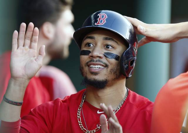 FILE - In this Friday, July 13, 2018 file photo,Boston Red Sox's Mookie Betts celebrates after scoring on a single by Brock Holt during the second inning of a baseball game against the Toronto Blue Jays in Boston. Boston's Mookie Betts and Milwaukee's Christian Yelich were runaway winners of the Most Valuable Player awards after the 26-year-old outfielders each led their teams to first-place finishes with dominant seasons that included batting titles. (AP Photo/Michael Dwyer, File)