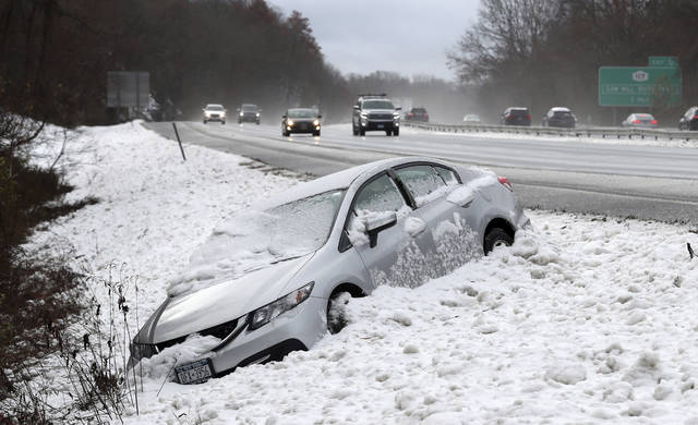 This Thursday, Nov. 15, 2018 photos shows traffic passing by as a car that went off Interstate 684, at the Goldens Bridge exit, during a snowstorm. The first snowfall of the season lingered Friday in the Northeast as thousands of exhausted commuters pointed their fingers at politicians and meteorologists for leaving them creeping along highways or stuck in mass transit hubs.  (Frank Bacerra Jr./The Journal News via AP)