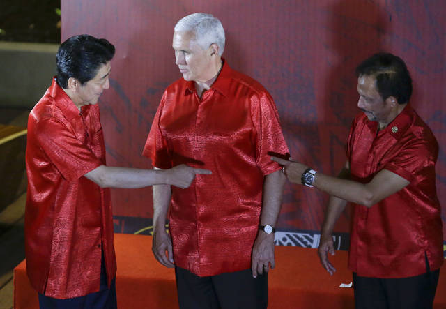 U.S. Vice President Mike Pence, center, watches Japanese Prime Minister Shinzo Abe, left, and Brunei Sultan Hassanal Bolkiah gesture before the start of the gala dinner family photo at the APEC summit in Port Moresby, Papua New Guinea, Saturday, Nov. 17, 2018. (AP Photo/Aaron Favila)
