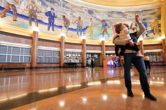 Visitors take in the architecture of the main hall as Cincinnati's historic Union Terminal reopens after a $224 million restoration, Saturday, Nov. 17, 2018, in Cincinnati. The Art Deco style terminal now houses museums, exhibits, a movie theater and a Cincinnati history library and archives. (AP Photo/John Minchillo)