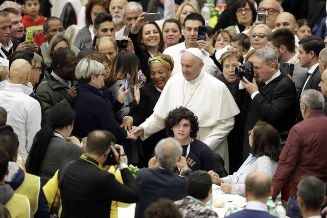 Pope Francis greets people as he arrives at a lunch, at the Vatican, Sunday, Nov. 18, 2018. Pope Francis is offering several hundred poor people, homeless, migrants, unemployed a lunch on Sunday as he celebrates the World Day of the Poor with a concrete gesture of charity in the spirit of his namesake, St. Francis of Assisi.(AP Photo/Andrew Medichini)