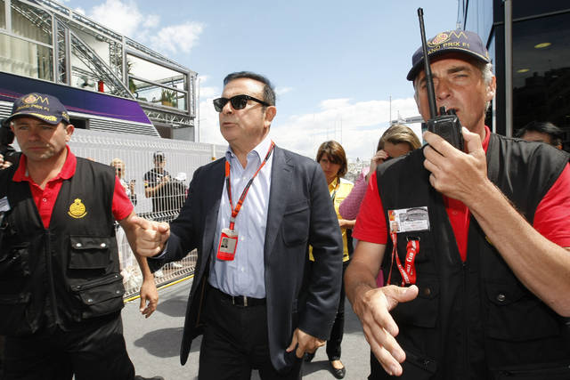 FILE - In this May 24, 2015, file photo, chairman and CEO of Renault-Nissan Carlos Ghosn, center, arrives prior to the start of the Formula One Grand Prix, at the Monaco racetrack. A trailblazer and visionary in the auto industry, Carlos Ghosn is also a highflyer prone to excesses that may have helped bring on his surprise downfall as head of the world's best-selling auto group. Ghosn was arrested last week in Japan for allegedly falsifying financial reports and misusing funds at Nissan Motor Co. It was a stunning reversal for the industry icon. (AP Photo/Claude Paris, File)