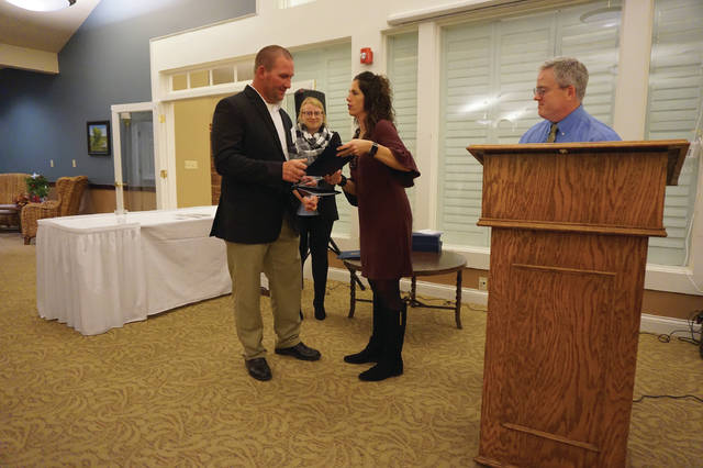 Tony Eisnnicher, owner of PJ's Family Restaurant, receives a Community Service Award from Sunbury/Big Walnut Area Chamber of Commerce President Cindy Erndt as Executive Director John Fox looks on.
