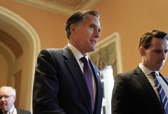 FILE - In this Nov. 14, 2018, file photo, Sen.-elect Mitt Romney, R-Utah, center, walks the hallway on Capitol Hill in Washington. Romney is a man in-between. He made it to Washington after all _ but not as president of the United States, the office he sought twice and other men won. He's not yet a senator from Utah, either, until he's sworn in Jan. 3.  (AP Photo/Pablo Martinez Monsivais, File)