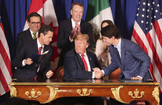 President Donald Trump, center, shakes hands with Canada's Prime Minister Justin Trudeau as Mexico's President Enrique Pena Nieto looks on after they signed a new United States-Mexico-Canada Agreement that is replacing the NAFTA trade deal, during a ceremony at a hotel before the start of the G20 summit in Buenos Aires, Argentina, Friday, Nov. 30, 2018. The USMCA, as Trump refers to it, must still be approved by lawmakers in all three countries. (AP Photo/Martin Mejia)