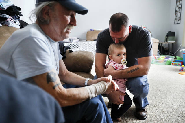 In this Nov. 28, 2018 photo, Tom Wolikow, right, holds his daughter Annabella alongside his father John, left, at their home in Warren, Ohio. It was working-class voters who bucked the area's history as a Democratic stronghold and backed Donald Trump in 2016, helping him win the White House with promises to put American workers first and bring back disappearing manufacturing and steel jobs. Whether they stick with him after this week's GM news and other signs that the economy could be cooling will determine Trump's political future.(AP Photo/John Minchillo)