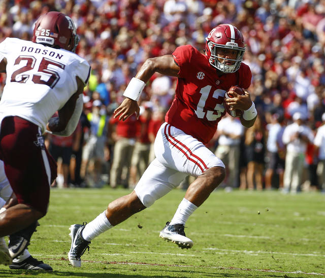 FILE - In this Sept. 22, 2018, file photo, Alabama quarterback Tua Tagovailoa (13) scrambles for a first down against Texas A&M during the first half of an NCAA college football game, in Tuscaloosa, Ala.  Tagovailoa is the offensive player of the year and one of five members of the top-ranked Crimson Tide to earn first-team honors on The Associated Press All-Southeastern Conference team, announced Monday, Dec. 3, 2018. (AP Photo/Butch Dill, File)