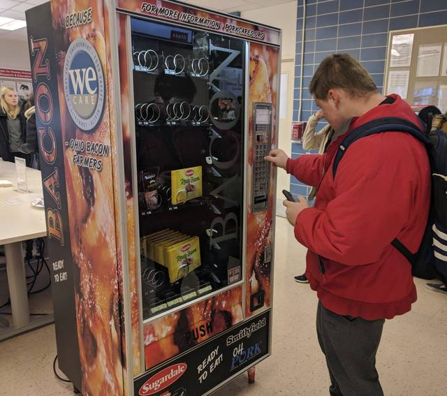 This Dec. 7, 2018 photo shows Ohio State University sophomore Nick Vales buys a package of bacon slices from a vending machine available on the Columbus campus.  The machine offers cooked bacon strips and bacon bits for $1. The Ohio Pork Council sponsored the machine, and it received bacon donations from Smithfield, Hormel and Sugardale. Proceeds from the machine will go toward Ohio State's meat science program.  [JD Malone/The Columbus Dispatch via AP)