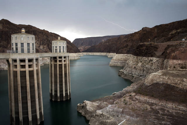 FILE - In this July 28, 2014, file photo, lightning strikes over Lake Mead near Hoover Dam that impounds Colorado River water at the Lake Mead National Recreation Area in Arizona. With drought continuing and reservoirs shrinking, several Southwestern U.S. states that depend on the Colorado River had been expected to ink a crucial share-the-pain contingency plan by the end of 2018. Officials now say they're not going to make it, at least not in time for upcoming meetings in Las Vegas involving representatives from Arizona, California, Colorado, Nevada, New Mexico, Utah, Wyoming and the U.S. government. (AP Photo/John Locher, File)