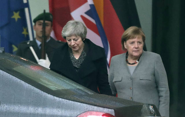 "British Prime Minister Theresa May, center, leaves after a meeting with German Chancellor Angela Merkel, right, in the chancellery in Berlin, Germany, Tuesday, Dec. 11, 2018. May is visiting several European countries to seek ""assurances"" on the Brexit agreement with the European Union to aid its passage through Britain's parliament. (AP Photo/Michael Sohn)"