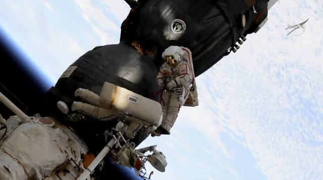 In this image from video made available by NASA, Russian cosmonaut Oleg Kononenko, right, and Sergei Prokopyev perform a spacewalk outside the Soyuz spacecraft attached to the International Space Station on Tuesday, Dec. 11, 2018. They are investigating a section where a mysterious leak appeared on Aug. 30. (NASA via AP)