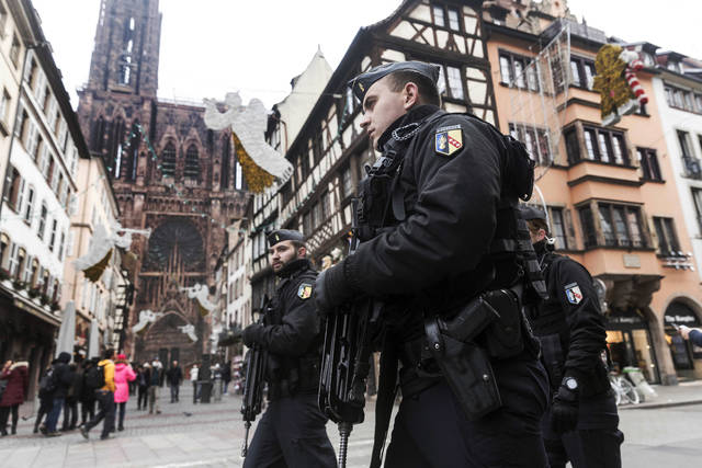 French police officers patrol next to Notre-Dame cathedral of Strasbourg following a shooting in the city of Strasbourg, eastern France, Wednesday, Dec. 12, 2018. A man who had been flagged as a possible extremist sprayed gunfire near the city of Strasbourg's famous Christmas market Tuesday, killing three people, wounding 12 and sparking a massive manhunt. France immediately raised its terror alert level. (AP Photo/Jean Francois Badias)