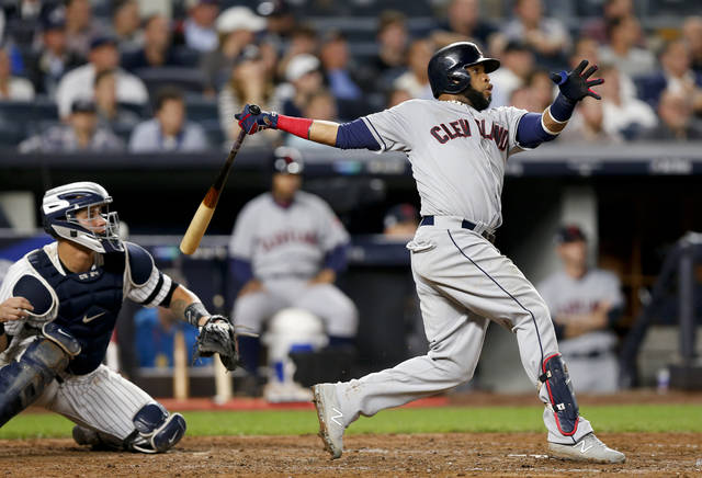 FILE - In this Oct. 9, 2017, file photo, Cleveland Indians' Carlos Santana (41) connects for a two-run home run against the New York Yankees during the fourth inning in Game 4 of baseball's American League Division Series, in New York. Edwin Encarnacion has been traded to Seattle and first baseman Carlos Santana has returned to the Indians in a three-team deal that also involved Tampa Bay. The Rays got infielder Yandy Diaz and minor league right-hander Cole Slusser from Cleveland. The Indians also acquired first baseman Jake Bauers. The swap came Thursday, Dec. 13, 2018, at the close of the winter meetings. (AP Photo/Kathy Willens, File)