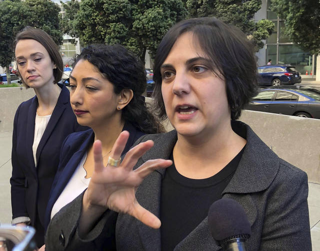 "Sirine Shebaya, an attorney for plaintiffs in a lawsuit accusing the administration of denying nearly all visa applicants under President Donald Trump's travel ban, speaks to reporters after a hearing in San Francisco Thursday, Dec. 13, 2018. Judge James Donato heard arguments on the administration's request that he dismiss the lawsuit. The case was ""not going away at this stage,"" he said at the close of the hearing. The plaintiffs say the administration is not honoring a waiver provision in the president's ban on travelers from five mostly Muslim countries - Iran, Lybia, Somalia, Syria and Yemen. (AP Photo/Sudhin Thanawala)"