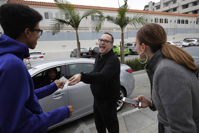 "In this Wednesday, Dec. 5, 2018 photo, Father Jim Sichko, center, gives Nicholas Vadi, left, a $100 bill to congratulate his birthday while buying lunch for customers at an In-N-Out Burger, in the Hollywood section of Los Angeles. ""My approach is not so much speaking about the word of God, although I do a lot of that, but showing the presence of God through acts of kindness that kind of shock the individual and kind of cause them to, maybe cause them to. stop for a little bit,"" he said. (AP Photo/Jae C. Hong)"