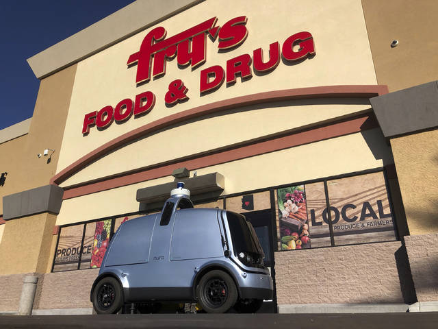 An autonomous vehicle called an R1 created to deliver groceries is displayed outside a Fry's grocery store, which is owned by Kroger Co., in Scottsdale, Ariz., Tuesday, Dec. 18, 2018. The fully autonomous vehicle is set begin piloting public roads Tuesday with no back up driver, though it will be monitored by humans in another automobile. (AP Photo/Brian Skoloff)