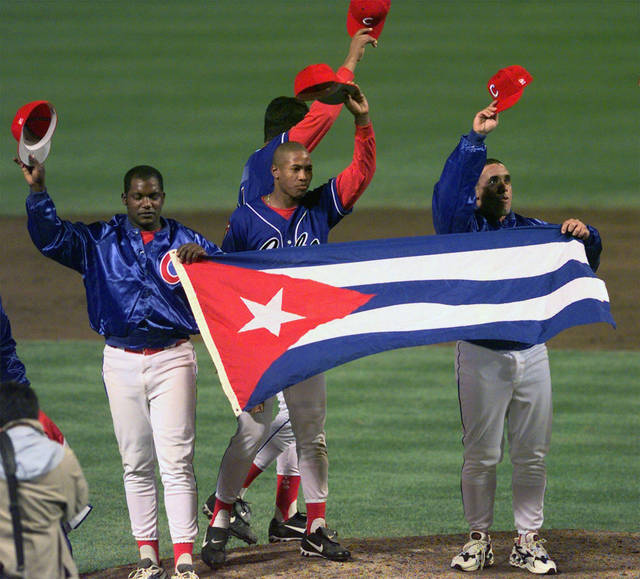 FILE - In this Monday, May 3, 1999 file photo, members of the Cuban baseball team carry their country's flag onto the field after a baseball game against the Baltimore Orioles at Camden Yards in Baltimore. Major League Baseball, its players' association and the Cuban Baseball Federation reached an agreement that will allow players from the island nation to sign big league contracts without defecting, an effort to eliminate the dangerous trafficking that had gone on for decades. The agreement runs through Oct. 31, 2021. (AP Photo/Nick Wass, File)