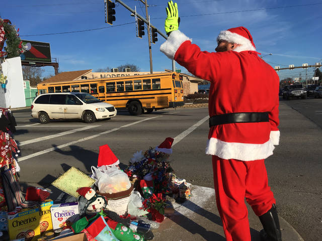 In this Dec. 18, 2018 photo, Jimmy Izbinski, wearing a Santa suit, waves to motorists passing the Christmas weed in Toledo, Ohio. The street corner weed decked out with lights and ornaments is spreading holiday goodwill. (AP Photo/John Seewer)