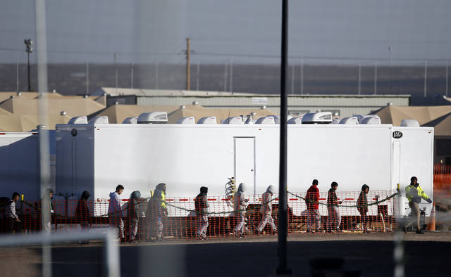 FILE - In this Dec. 13, 2018 file photo migrant teens walk in a line through the Tornillo detention camp in Tornillo, Texas. The Trump administration says it will keep the tent city holding more than 2,000 migrant teenagers open through early 2019. The announcement was made Wednesday, Dec. 26, 2018 about the Tornillo facility, which opened in June in an isolated corner of the Texas desert for up to 360 children. (AP Photo/Andres Leighton, file)