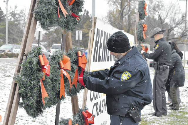 City of Delaware Police Officer Robert Hatcher places a name on a wreath Nov. 29.