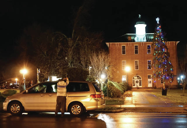 The Village of Sunbury's Christmas tree was lit during Christmas on the Square on Dec. 1. Two nights later, a family puts a tree they purchased on top of their vehicle as the tree remains lit.