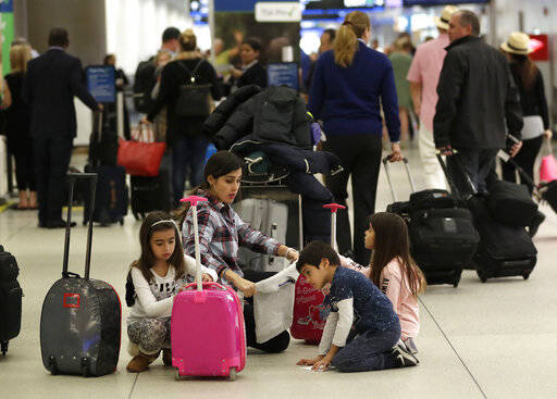 Travelers organize their luggage before entering a security checkpoint at Miami International Airport, Friday, Jan. 18, 2019, in Miami. The three-day holiday weekend is likely to bring bigger airport crowds. (AP Photo/Lynne Sladky)