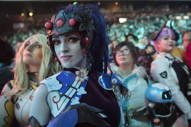 FILE - In this July 28, 2018 file photo, cosplayer fans watch the competition between Philadelphia Fusion and London Spitfire during the Overwatch League Grand Finals competition, at Barclays Center in the Brooklyn borough of New York.  Most professional esports are devoid of female players at their highest levels, even though 45 percent of U.S. gamers are women or girls. Executives for titles like League of Legends and Overwatch say they are eager to add women to pro rosters, but many female gamers say they're discouraged from chasing such careers by toxic behavior and other barriers. (AP Photo/Mary Altaffer, File)