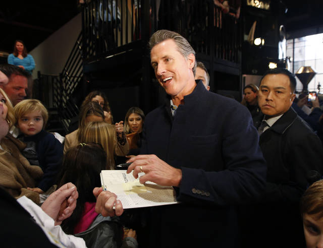 Governor-elect, Lt. Gov. Gavin Newsom, center, autographs a copy of his book, Citizenville for a well-wisher while attending a pre-inaugural Family Event held at the California Railroad Museum, Sunday, Jan. 6, 2019, in Sacramento, Calif. Newsom will be sworn-in as California's 40th governor, Monday. (AP Photo/Rich Pedroncelli)