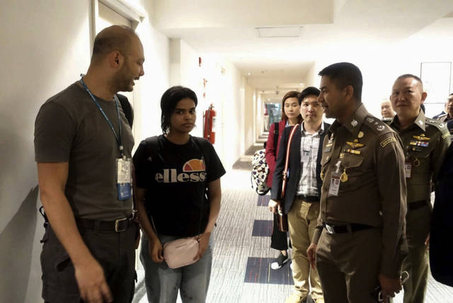 In this photo released by the Immigration Police, Chief of Immigration Police Maj. Gen. Surachate Hakparn, right talks to Saudi woman Rahaf Mohammed Alqunun,second left, before leaving the Suvarnabhumi Airport in Bangkok Monday, Jan. 7, 2019. A Saudi woman who says she is fleeing abuse by her family and wants asylum in Australia has sent out desperate pleas for help over social media. Rahaf Mohammed Alqunun, 18, began posting on Twitter late Saturday after her passport was taken away when she arrived on a flight from Kuwait. (Immigration police via AP)