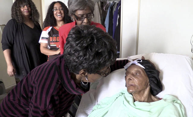 FILE - In this Sept. 22, 2018 file photo, Lessie Brown, right, is visited by her daughters, Verline Wilson, foreground, and Vivian Hatcher, third from left, and other family and friends at her home in Cleveland Heights, Ohio. A grandson said Brown, the 114-year-old Ohio woman who was believed to be the oldest person in the United States, died Tuesday. Jan. 8, 2019. (David Petkiewicz/The Plain Dealer via AP)