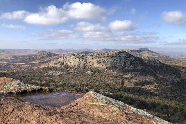 In this Dec. 31, 2018 photo, clouds cast shadows in the Wichita Mountains Wildlife Refuge in Comanche County, Okla. The U.S. Fish and Wildlife Service is directing dozens of wildlife refuges including this one to make sure hunters and others have access despite the government shutdown, according to an email obtained Wednesday by The Associated Press.   (AP Photo/Adam Kealoha Causey)
