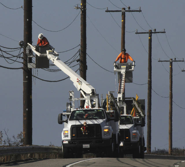 FILE - In this Sunday, Nov. 25, 2018 file photo, utility crews repair overhead lines along the Pacific Coast Highway just west of Malibu, Calif., where the Woolsey Fire burned down from the Santa Monica Mountains to the water's edge at Leo Carrillo State Beach. To prevent wildfires, Pacific Gas & Electric Co. should re-inspect its entire electric grid and cut off power during certain wind conditions regardless of the inconvenience to customers or loss of profit, a U.S. judge proposed Wednesday, Jan. 9, 2019. (AP Photo/John Antczak, File)
