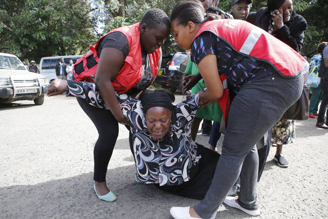 Kenya Red Cross personnel helps a woman reacting after learning of a family member killed during a recent terrorist attack Wednesday, Jan. 16 2019, at the Chiromo Mortuary, Nairobi, Kenya. An upscale hotel complex in Kenya's capital came under attack on Tuesday, with a blast and heavy gunfire. The al-Shabab extremist group based in neighboring Somalia claimed responsibility and said its members were still fighting inside (AP Photo/Brian Inganga)