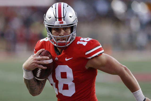 """FILE - In this Sept. 22, 2018, file photo, Ohio State quarterback Tate Martell runs against Tulane during an NCAA college football game in Columbus, Ohio. Martell says he is transferring from Ohio State to Miami. Martell announced on Twitter early Wednesday, Jan. 16: """"I'm a Hurricane."""" Martell had entered his name into the NCAA transfer portal last week and was free to be approached by schools about a potential transfer. (AP Photo/Jay LaPrete, File)"""