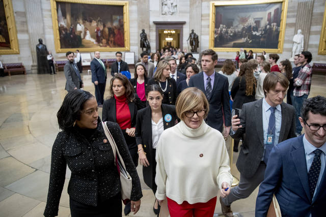 In this Jan. 16, 2019, photo, freshman Congressmen led by Rep. Susie Lee, D-Nev., center, walk through the Capitol Rotunda as they deliver a letter calling to an end to the government shutdown to the office of Senate Majority Leader Mitch McConnell of Ky., on Capitol Hill in Washington. Also pictured is Rep. Alexandria Ocasio-Cortez, D-N.Y., center left, Rep. Veronica Escobar, second from left, and at front left Rep. Jahana Hayes, D-Conn. Two weeks into their congressional careers, newly elected House Democrats are cutting different paths on Capitol Hill. (AP Photo/Andrew Harnik)