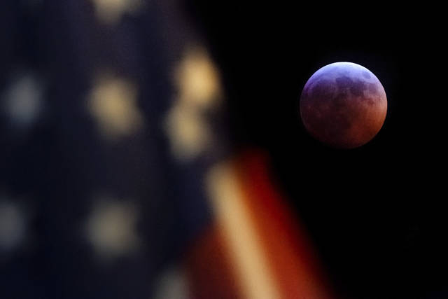 A U.S. Flag in downtown Washington flies in front of the moon during a lunar eclipse, Sunday, Jan. 20, 2019. The entire eclipse will exceed three hours. Totality - when the moon's completely bathed in Earth's shadow - will last an hour. Expect the eclipsed, or blood moon, to turn red from sunlight scattering off Earth's atmosphere. (AP Photo/J. David Ake)