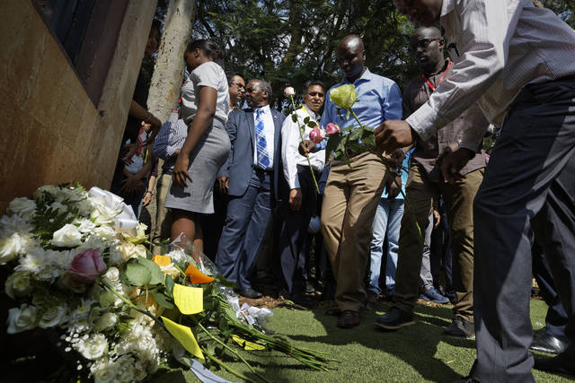 Staff lay flowers in honor of the dead outside the gate of the dusitD2 hotel complex which was attacked last week, at a wreath-laying event organized by the hotel complex management in Nairobi, Kenya Tuesday, Jan. 22, 2019.  The ceremony took place at 3:05pm on Tuesday, exactly a week after the attack by gunmen and a suicide bomber on the hotel and office complex in Kenya's capital. (AP Photo/Ben Curtis)